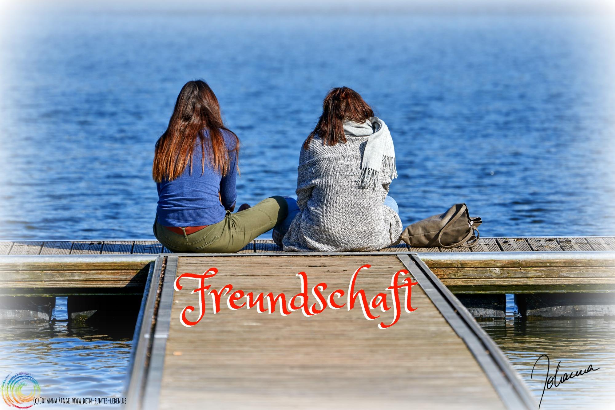Das Wort Freundschaft auf einem Photo von zwei Menschen, die auf einem Steg am Wasser sitzen. (c)2018 Johanna Ringe www.dein-buntes-leben.de
